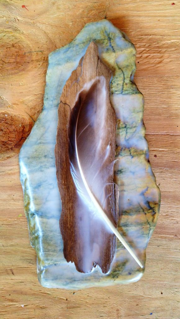 Feather and wood on stone